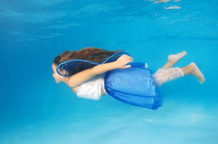 fifteen year old: Girl presenting underwater fashion in pool