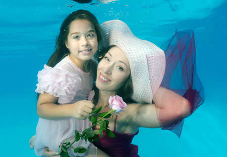 underwater pool: Woman and girl presenting underwater fashion in pool