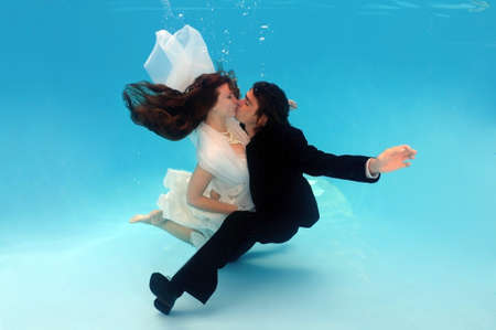 age 25 30 years: Bride and groom kissing, underwater wedding in a pool Stock Photo