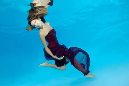 fas: Young beautiful woman with long hair in a long red dress under water, underwater fashion in the pool, Odessa, Ukraine