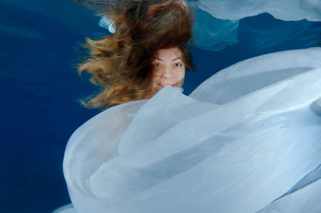 craze: Young beautiful woman with long hair in a long white dress under water, underwater fashion in the pool, Odessa, Ukraine Stock Photo