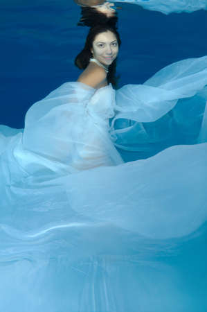 fas: Young beautiful woman with long hair in a long white dress under water, underwater fashion in the pool, Odessa, Ukraine Stock Photo