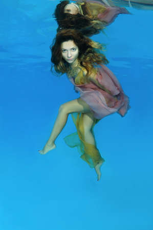 Young beautiful woman with long hair in a bright dress under water, underwater fashion in the pool, Odessa, Ukraine
