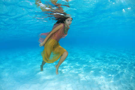 against the current: Young beautiful woman with long hair in a bright dress woman goes against the current under water, underwater fashion in the Indian Ocean, Maldives Stock Photo