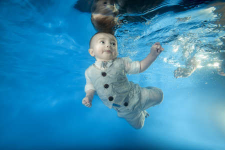 little boy in a costume swims underwater in the pool