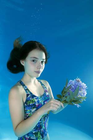 Onderwater portret meisje met een bloem