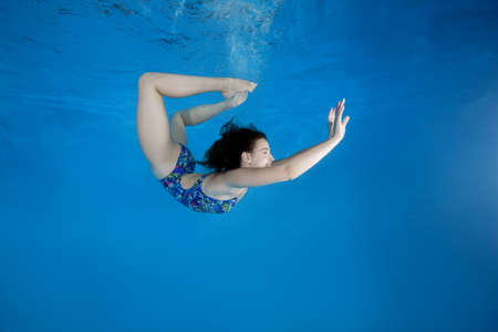 Girl curled into a wheel under water in the pool. Underwater acrobatics Stockfoto