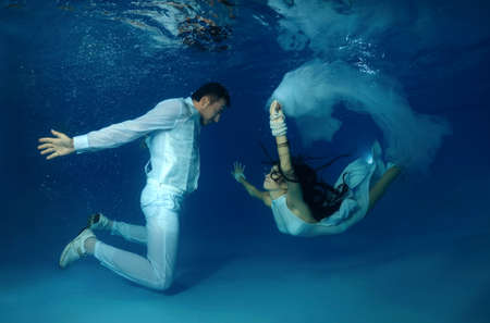 Bride and groom in a white wedding dress swim to each other underwater in the pool. Underwater wedding