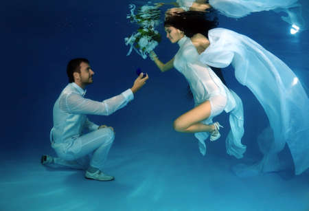 Groom kneeling offers the bride an engagement ring underwater in the pool. Underwater wedding  Banque d'images