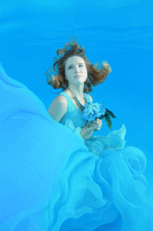 Young beautiful woman in a pale blue dress with a bouquet of flowers posing under water (for the calendar, spring, March)