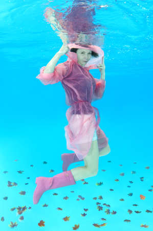 Young beautiful woman in a pink raincoat and pink rubber boots posing under water (for the calendar, autumn, November) 版權商用圖片