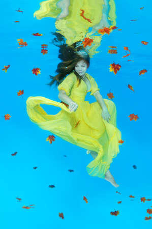 Golden Autumn - Young beautiful woman in bright yellow dress posing under water (for the calendar, autumn, October)