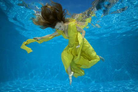 Young pregnant woman in a bright yellow dress posing underwater