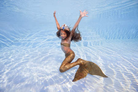 A girl in a mermaid costume poses underwater in a pool