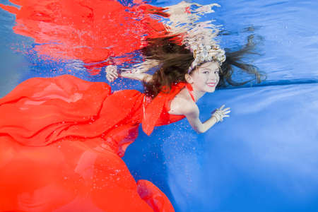 Girl in long, bright dresses wearing poses underwater