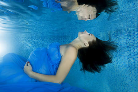 A pregnant woman in a blue dress looks at her reflection by the underwater in the pool Imagens