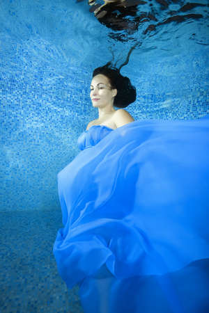 Pregnant woman in a blue dress posing underwater in the pool