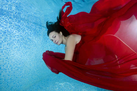 Pregnant woman in a red dress dives underwater in the pool Imagens