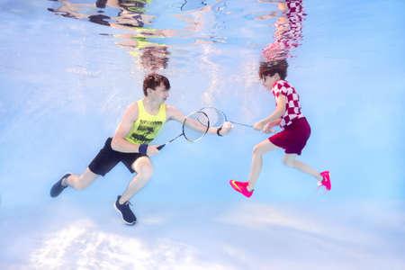 Two teenagers playing badminton underwater Stock Photo