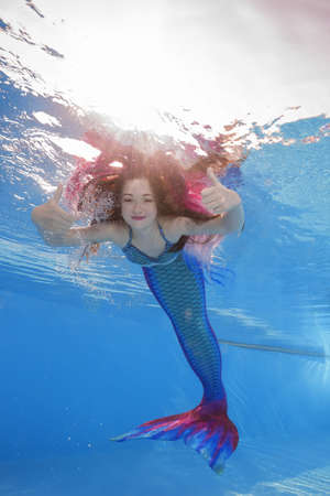 1f6a649c3c64c A girl in a mermaid costume poses underwater in a pool
