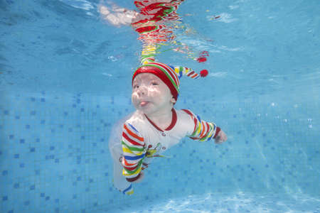 3 months old boy in a bright striped swimming suit swims underwater in the pool