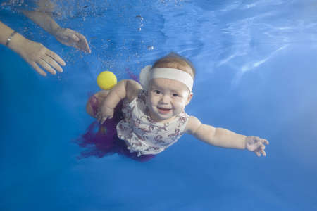 Little girl in a dress playing with a ball underwater in the pool Stock Photo