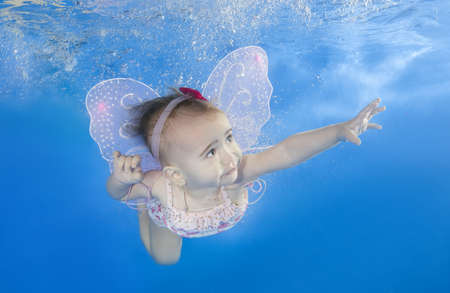 Little baby learns to swims underwater. Baby swimming underwater in the pool on a blue water background. Healthy family lifestyle and children water sports activity.