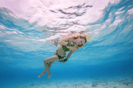 Golden-haired nymph swim underwater surface in blue water, Indian Ocean, Maldives