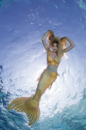 Golden-haired mermaid swims underwater surface in blue water, Indian Ocean, Maldives