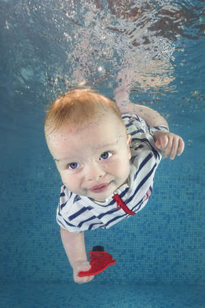 Little baby boy in a striped suit with toy learns to swims underwater in the swimming pool. Healthy family lifestyle and children water sports activity. Child development, disease prevention