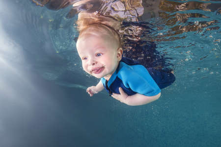 Little baby boy in a blue wetsuit learns to swims underwater in the swimming pool. Healthy family lifestyle and children water sports activity. Child development, disease prevention