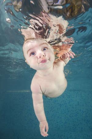 Little baby boy learning to swim underwater in a swimming pool. Healthy family lifestyle and children water sports activity. Child development, disease prevention