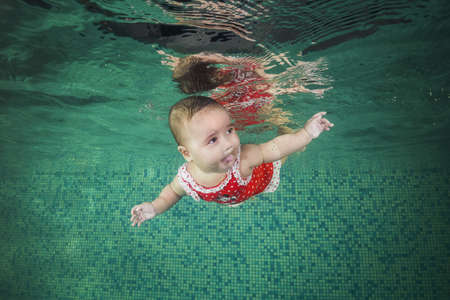 A little girl in red swimmiing suit learns to swim underwater in the pool. Baby swimming underwater in the pool. Healthy family lifestyle and children water sports activity. Child development, disease 写真素材