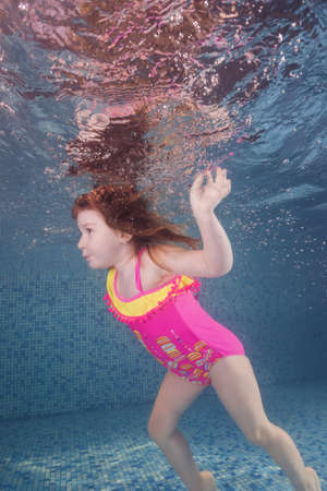 Girl in pink swimsuit playing underwater in the pool floats and spins among the air bubbles. Healthy family lifestyle and children water sports activity. Child development, disease prevention
