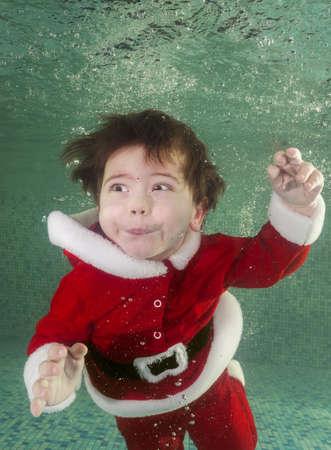 Boy in santa costume dives underwater in the pool 写真素材