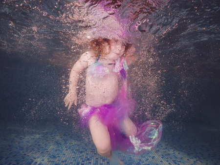 Girl playing underwater in the pool floats and spins among the air bubbles. Healthy family lifestyle and children water sports activity. Child development, disease prevention