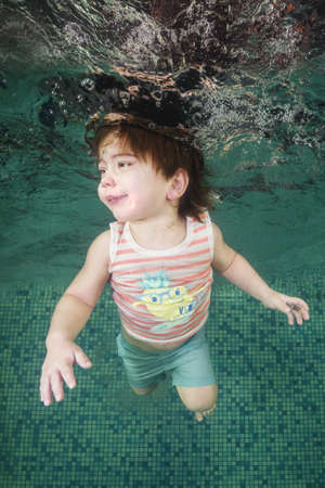 A little boy learns to swim underwater in the pool. Healthy family lifestyle and children water sports activity. Child development, disease prevention