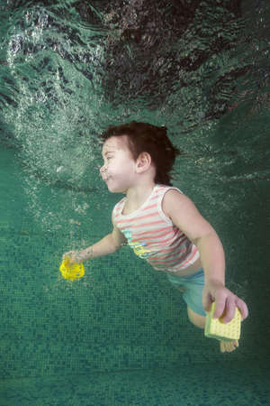 A little boy with toy learns to swim underwater in the pool. 2-3 years,  Healthy family lifestyle and children water sports activity. Child development, disease prevention 写真素材
