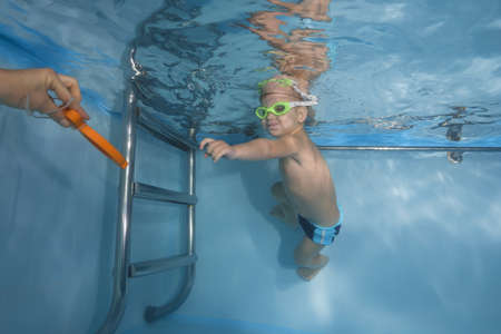 Boy in glasses plays with a toy under water in the pool. Healthy family lifestyle and children water sports activity. Child development, disease prevention