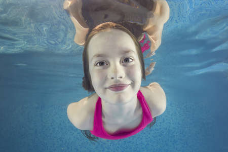 Portrait of a smiling teen girl in pink swimsuit smims underwater in a swimming pool