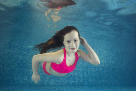 Girl in pink swimsuit smims underwater in the swimming pool. 写真素材