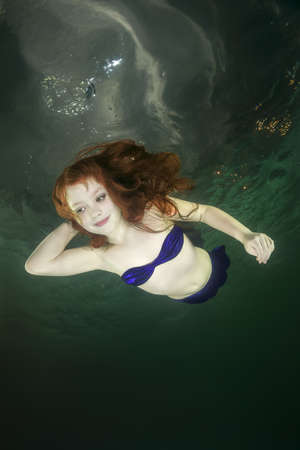 Young red-haired mermaid swims underwater 写真素材