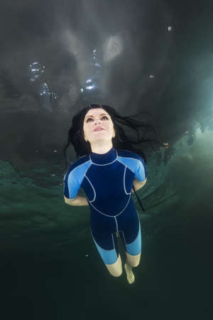 Woman in a diving suit swim underwater in the swimming pool
