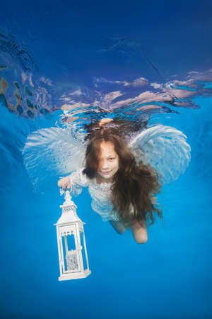 White angel with a flashlight underwater. Underwater girls pictures Фото со стока