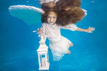 White angel with a flashlight underwater. Underwater girls pictures 写真素材