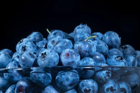 Fresh blueberries in in glassware on black background. Close-up of Bog bilberry, bog blueberry, northern bilberry or western blueberry (Vaccinium uliginosum)