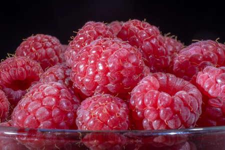 Close-up of European raspberry or red raspberry (Rubus idaeus) on black background.