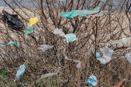 Closeup of face masks and plastic debris on branches of trees. Coronavirus (COVID-19) is contributing to pollution, as discarded face masks clutter parks & streets of the city along with plastic trash