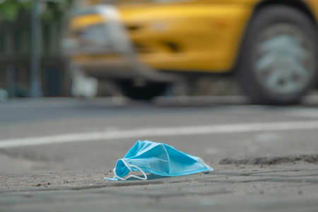 Discarded medical face mask lies on the sidewalk, and cars are driving in the background. Face masks polluting streets of the city since Coronavirus COVID-19. Soft focus.