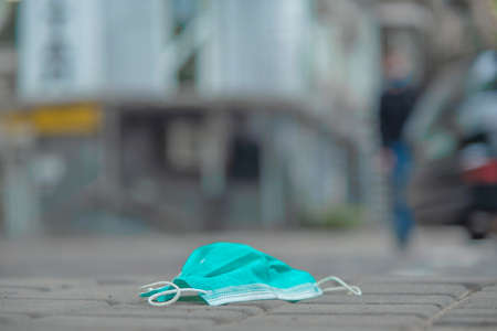 Discarded medical face mask lies on the sidewalk. Face masks polluting streets of the city since Coronavirus COVID-19. Soft focus. Reklamní fotografie